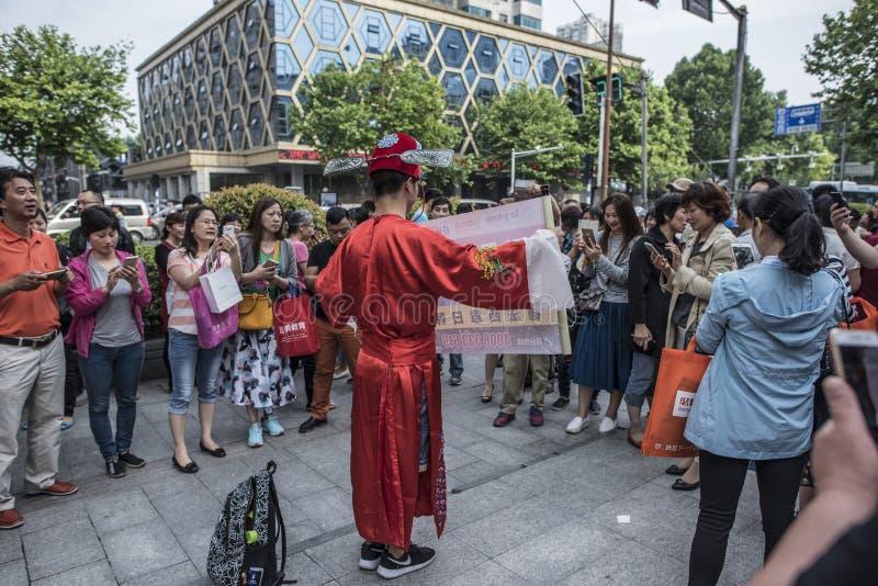 Un personal de la institución de la enseñanza de idiomas lleva un traje del campeón y recomienda cursos del idioma extranjero a l fotos de archivo libres de regalías