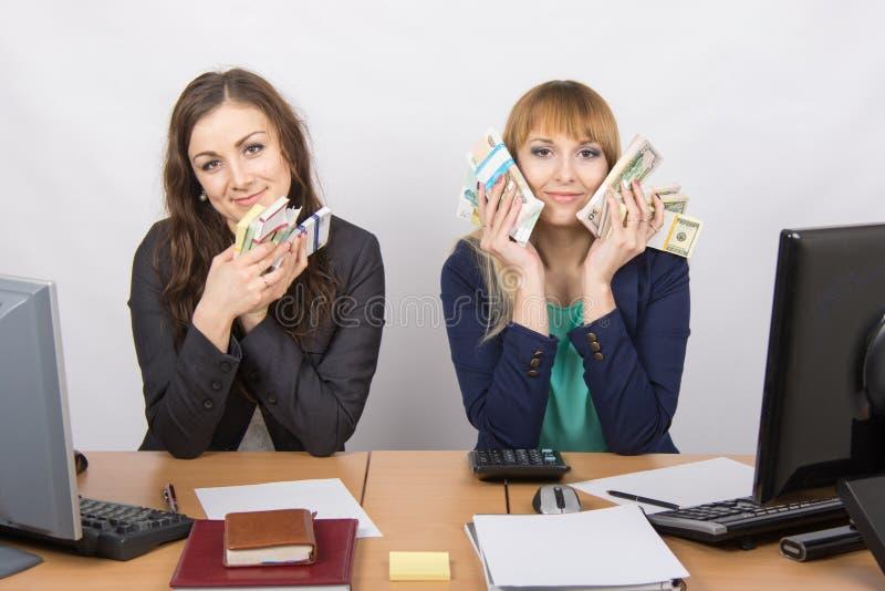Un personale di due uffici ai soldi dell'abbraccio della tavola imballa fotografie stock libere da diritti