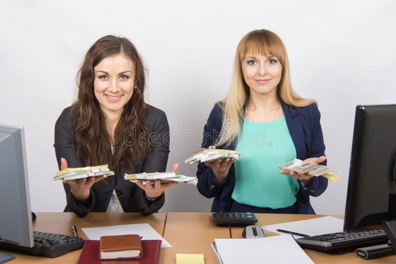 Un personale di due uffici alla tavola sta tenendo un pacchetto di soldi fotografie stock