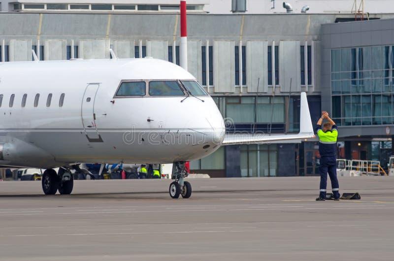 Un personnel de piste de contrôleur du trafic d'aéroport guidant un avion sur une piste d'aéroport images stock