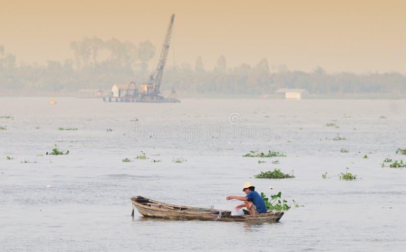 Un pescado de cogida del hombre en el río Mekong en Tra Vinh, Vietnam imágenes de archivo libres de regalías
