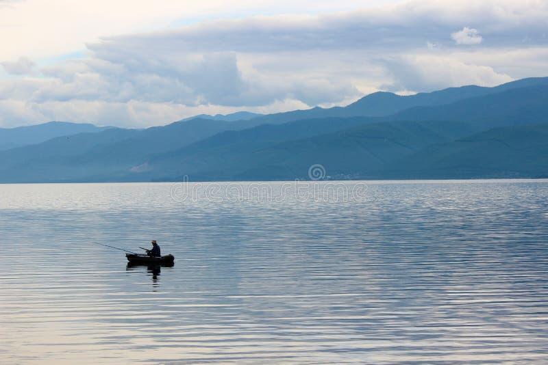 Un pescador en el barco imagenes de archivo