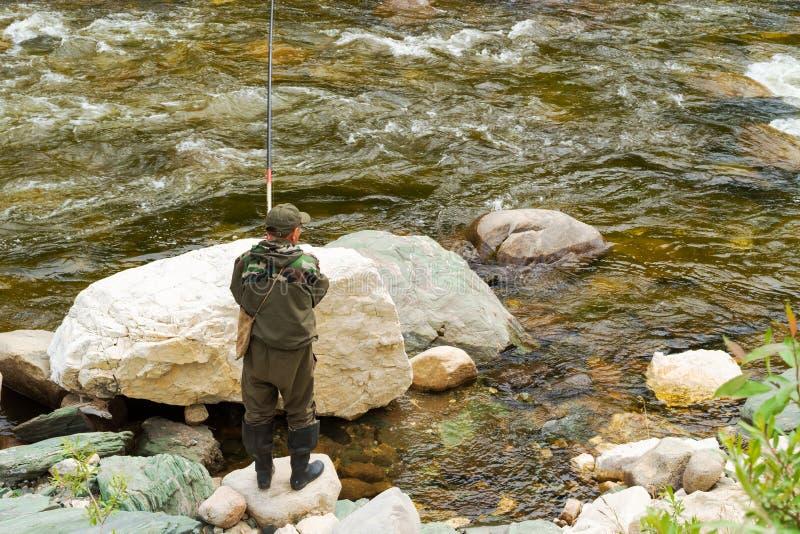 Un pescador en un río de la montaña imagenes de archivo