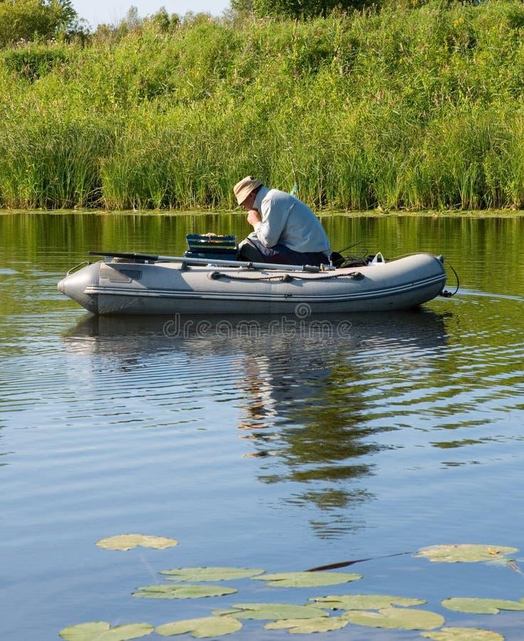 Un pescador en un barco de goma fotos de archivo