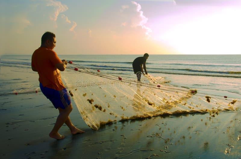 Un pescador está levantando un próximo neto una playa imagen de archivo libre de regalías