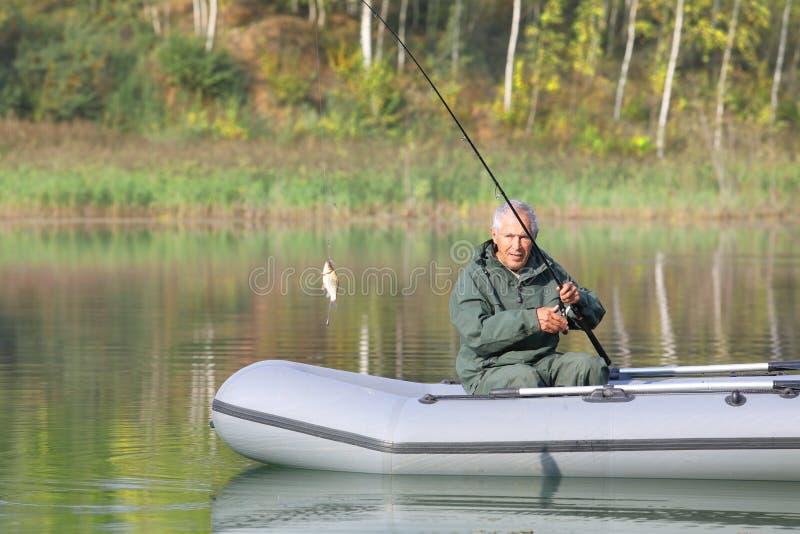 Un pescatore anziano ha preso appena un carassio fotografia stock libera da diritti