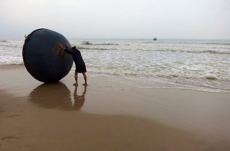 Un pescatore che asciuga la sua barca del canestro sulla riva di mare un giorno tempestoso immagini stock libere da diritti