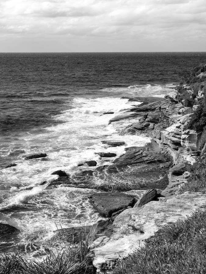 Un pescatore che pesca su una spiaggia rocciosa su una bella mattina fotografie stock libere da diritti