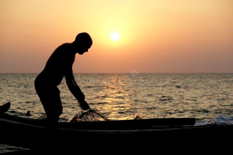 Un pescatore con una barca sulla riva dell'oceano al tramonto L'India fotografie stock libere da diritti