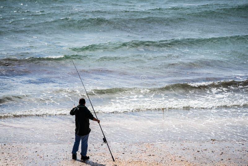 Un pescatore con una canna da pesca a Fenella Beach in buccia, Isola di Man immagine stock
