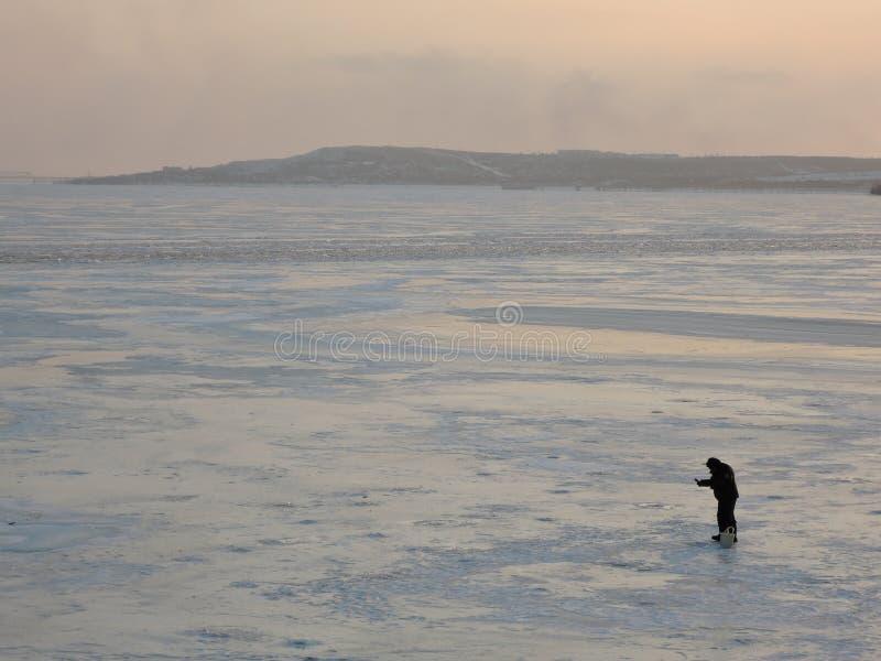 Un pescatore dell'inverno su ghiaccio sta pescando fotografia stock libera da diritti