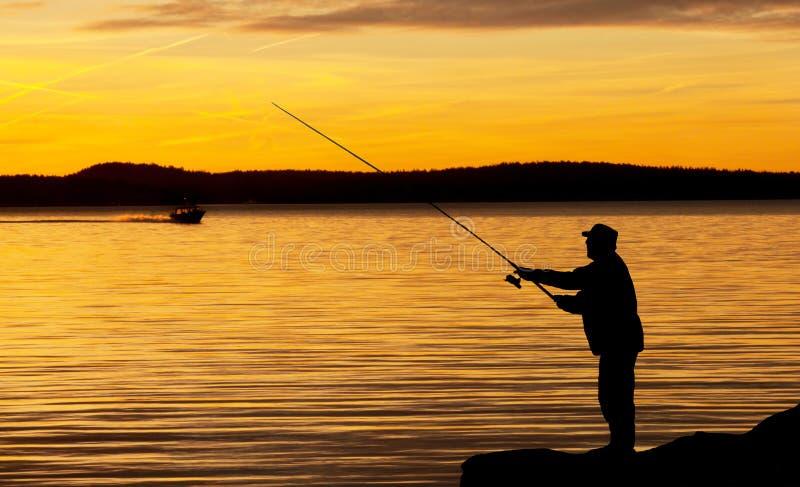 Un pescatore nel tramonto. fotografia stock