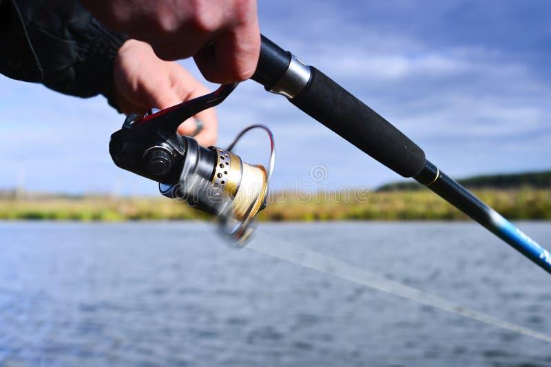 Un pescatore pesca un pesce Primo piano di filatura della bobina Profondità di campo bassa sulla bobina della linea di pesca fotografia stock