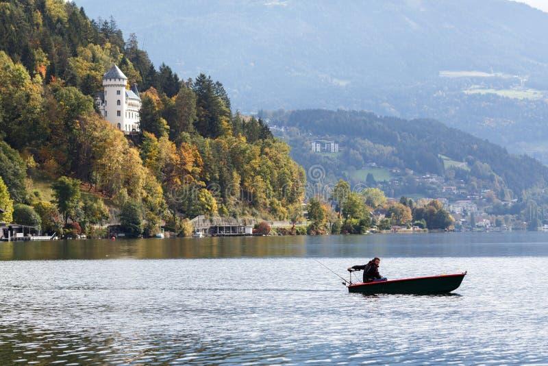 Un pescatore solo in un'imbarcazione a motore sul lago Millstatt l'austria immagini stock libere da diritti