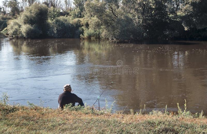 Un pescatore sulla riva di piccolo fiume fotografie stock
