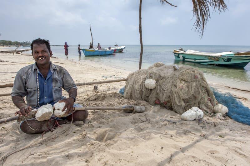 Un pescatore tende alle sue reti sulla spiaggia della costa ovest sull'isola di Delft nella regione di Jaffna di Sri Lanka immagine stock