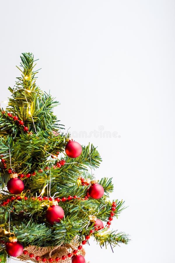Un petit arbre de Noël vert décoré d'une guirlande des lumières lumineuses avec les boules rouges sur un fond blanc photos libres de droits