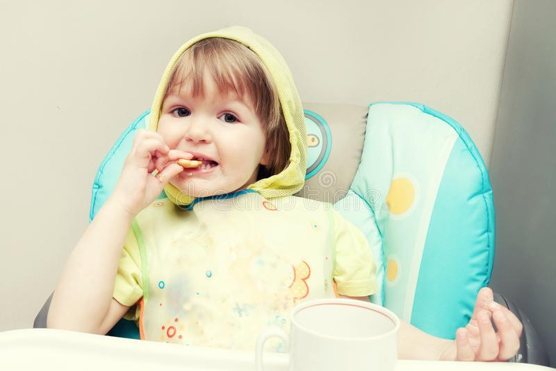 Un petit bébé d'un an mange au highchair images libres de droits