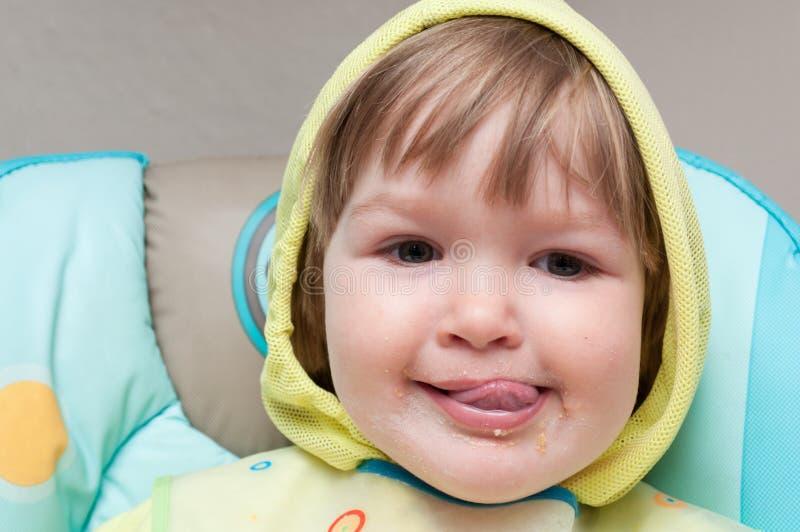 Un petit bébé d'un an mange le highchair photo libre de droits