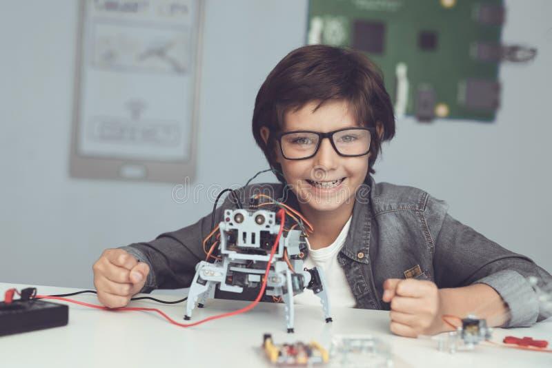 Un petit ballot en verres tient un robot Le garçon regarde très heureux images libres de droits
