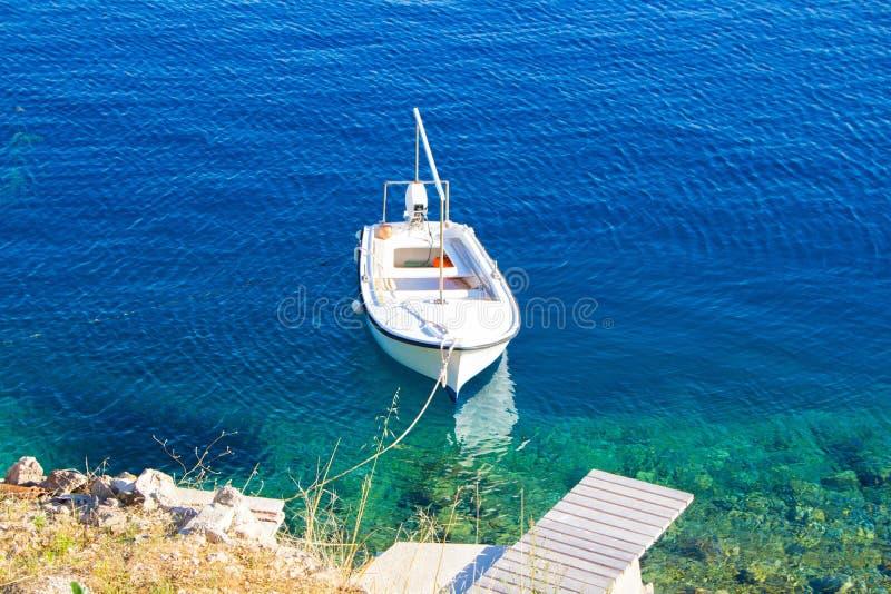 Un petit bateau de pêche blanc attaché au pilier Bateau blanc en mer claire bleue, photo pittoresque Le bateau se tient près du r photographie stock