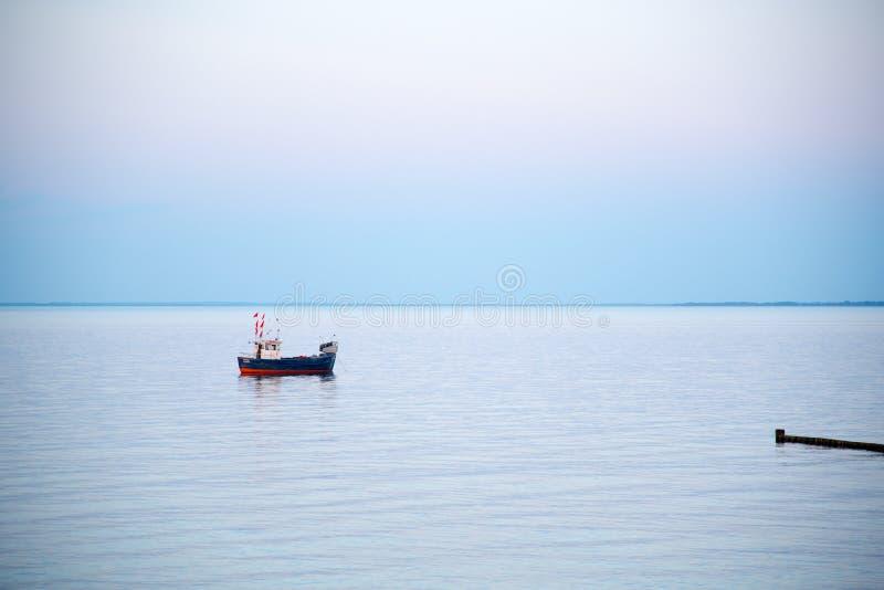 Un petit bateau de pêche sur la mer pendant le début de la matinée photographie stock libre de droits