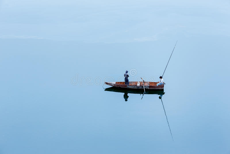 Un petit bateau isolé avec deux jeunes pêcheurs photos stock