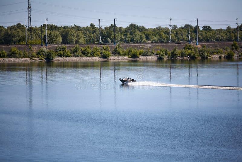 Un petit bateau navigue le long de la rivière un jour ensoleillé d'été image libre de droits