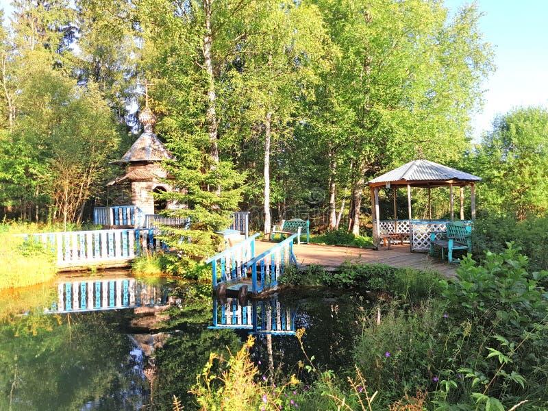 Un petit belvédère par l'étang et une vieille chapelle dans les bois image libre de droits