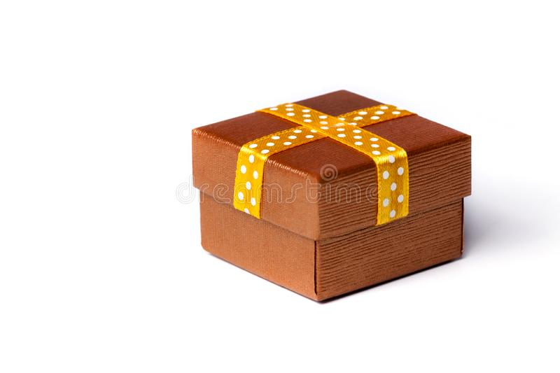 Un petit bo?te-cadeau d'or classique ferm? de surprise avec un ruban, pr?sentent pour n'importe quelle occasion Le concept de bo? image stock
