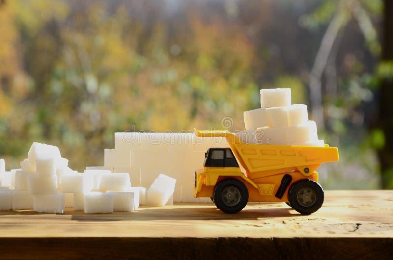 Un petit camion jaune de jouet est chargé avec des cubes en sucre blanc près des débris de sucre Une voiture sur une surface en b image libre de droits