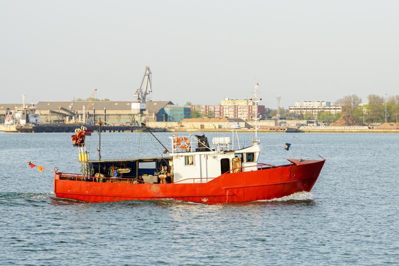 Un petit chalutier de pêche revient au port photographie stock