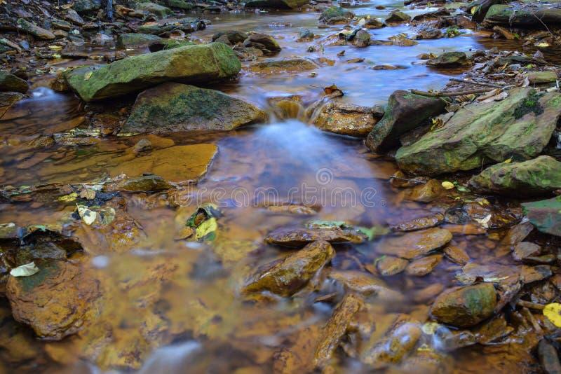 Un petit courant a souillé l'orange du drainage de mine acide photo stock