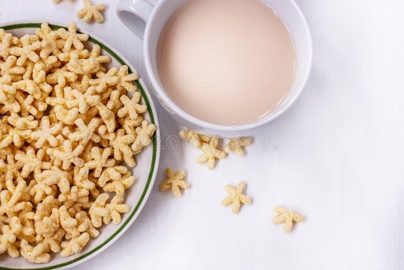 Un petit déjeuner sain des flocons, du lait et du thé d'avoine sur une table blanche image libre de droits