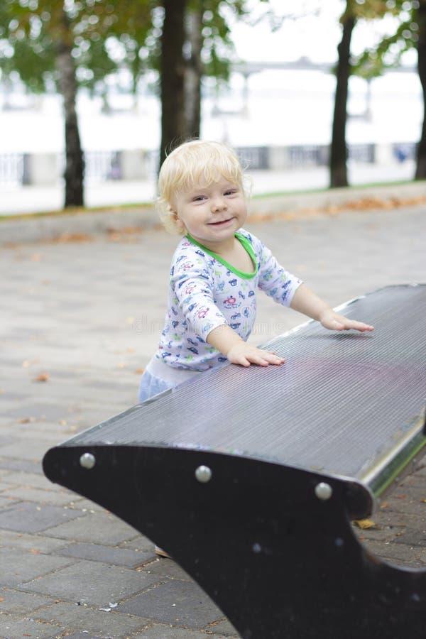 Un petit enfant apprend à marcher près des bancs, enfant en bas âge photographie stock libre de droits