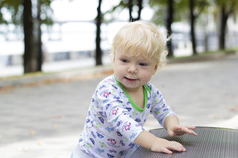 Un petit enfant apprend à marcher près des bancs, enfant en bas âge image libre de droits