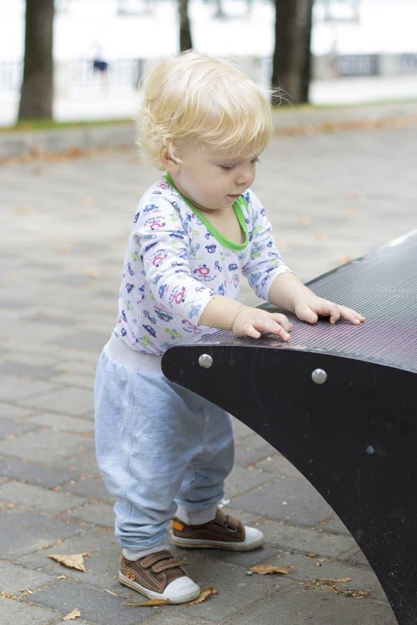 Un petit enfant apprend à marcher près des bancs, enfant en bas âge image stock