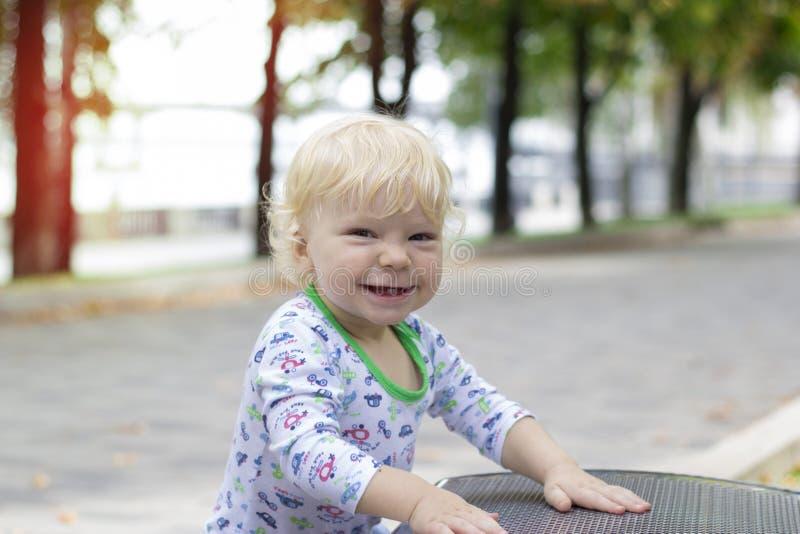 Un petit enfant apprend à marcher près des bancs, enfant en bas âge photo libre de droits