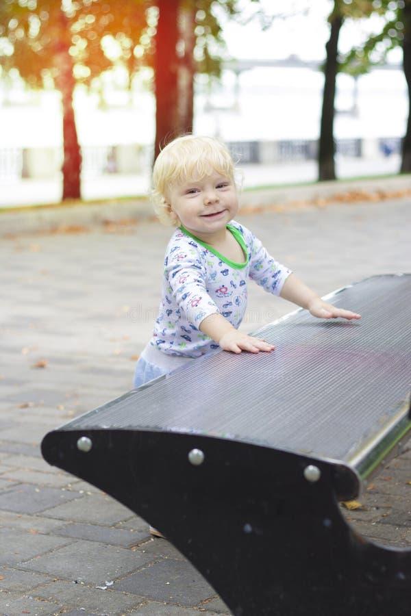 Un petit enfant apprend à marcher près des bancs, enfant en bas âge images libres de droits