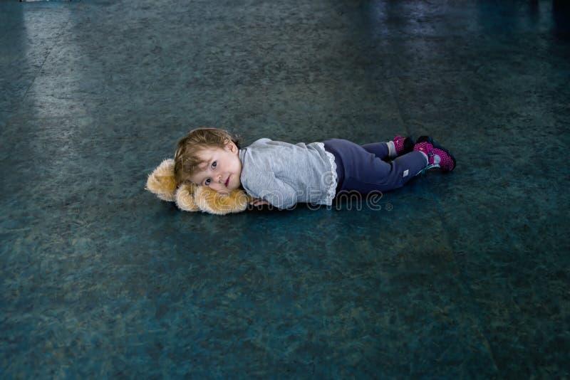 Un petit enfant couché sur le sol froid avec son jouet sous la tête images libres de droits