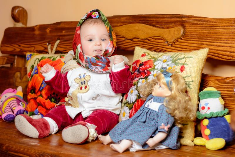 Un petit enfant dans un châle se reposant sur un sofa avec les oreillers brodés image stock