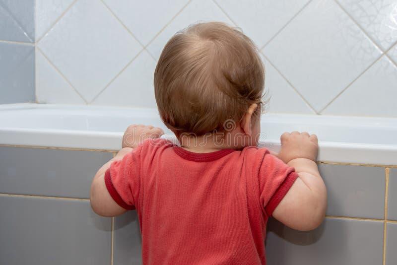 Un petit enfant dans la salle de bains examinant le bain, tenant le bord photographie stock