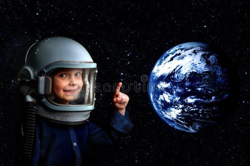 Un petit enfant s'imagine pour être un astronaute dans le casque d'un astronaute photo stock