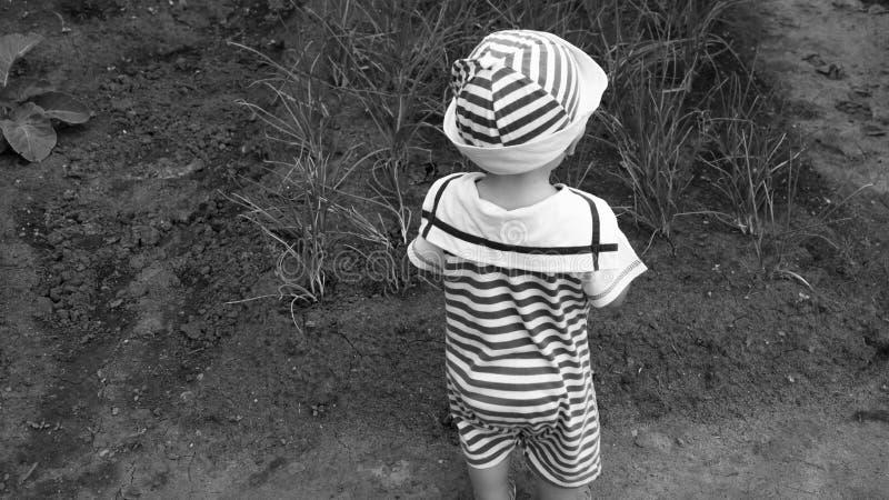 Un petit enfant se tient dans le jardin photographie stock