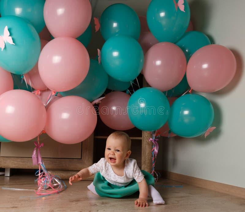 Un petit enfant, une fille, un bébé, s'assied sur le plancher dans une robe blanche et bleue, sur un fond d'air bleu et rose, des photos stock