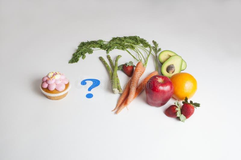 Un petit gâteau contre Fruits et légumes avec un point d'interrogation photos stock