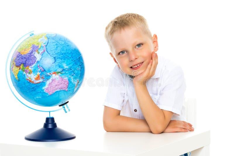 Un petit garçon étudie la géographie sur un globe photos stock
