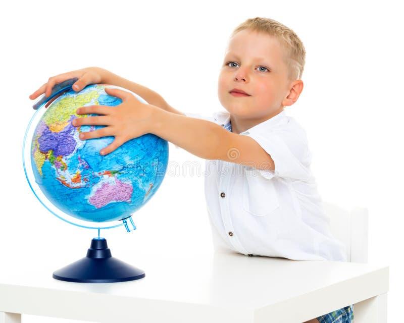 Un petit garçon étudie la géographie sur un globe photo stock
