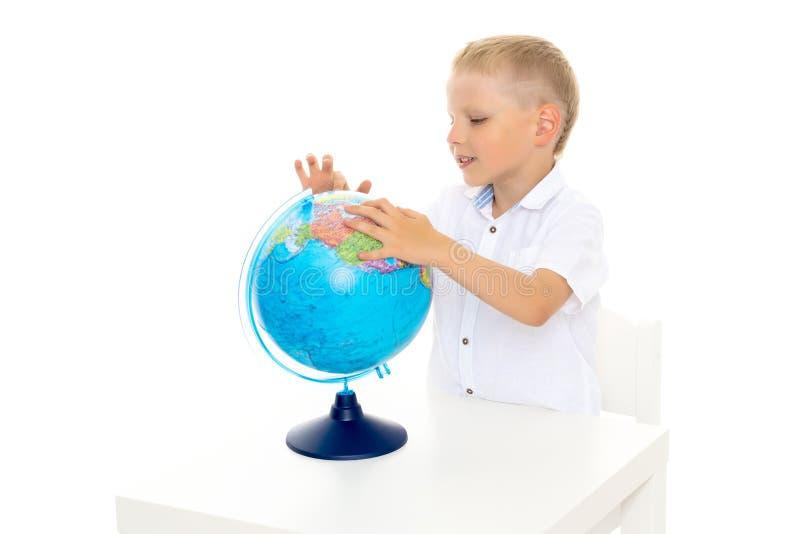 Un petit garçon étudie la géographie sur un globe photographie stock libre de droits