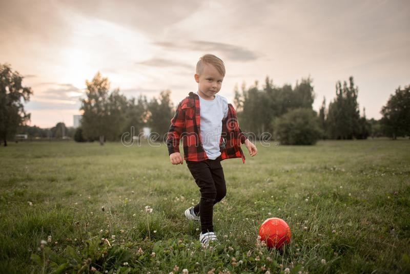 Un petit garçon avec un football avec son chien photo libre de droits